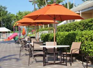 Three orange umbrellas covering patio tables