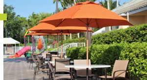 Three orange umbrellas covering patio tables