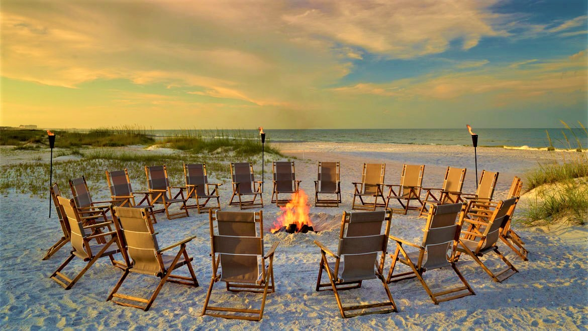 Deck chairs around a fire on the beach