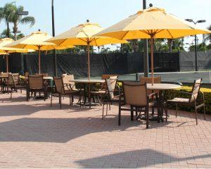 Yellow umbrellas by tennis court