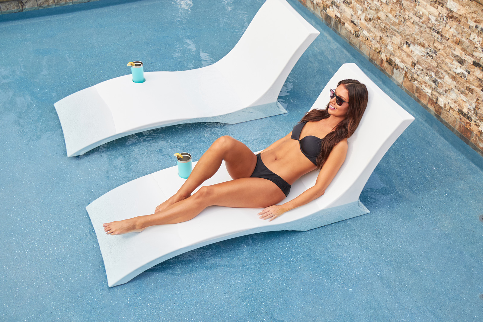 Woman laying on chaise in pool