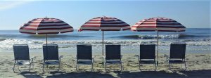 3 chairs and striped umbrellas on beach